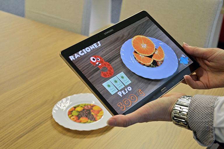 Una aplicación de realidad aumentada desarrollada por investigadores de la Universitat Politècnica de Valencia (España), enseña a los niños diabéticos a relacionar alimentos con raciones de hidratos de carbono, ya que de su consumo depende el incremento de la glucemia después de las comidas.EFE/ (Foto cedida)