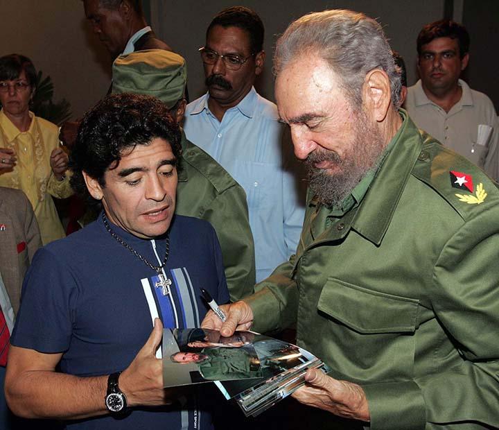 """EFE/CONO SUR HAB17 LA HABANA (CUBA) 27/10/05.- El ex futbolista argentino Diego Armando Maradona (izq) y el presidente cubano Fidel Castro (der) observan varias fotos donde aparecen juntos, despuÈs de comparecer en el programa televisivo ìMesa Redondaî ayer, jueves 27 de octubre, en La Habana. Maradona viajÛ esta semana a Cuba para entrevistar a Castro para su programa """"La Noche del 10"""". EFE/Ismael Francisco/AIN"""