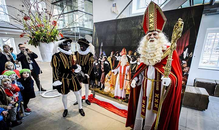 """HOLANDA ARTE:AMS01 AMSTERDAM (HOLANDA) 02/12/2015 .- San Nicol·s (d) y Zwarte Piet (Pedro Negro) (i) enseÒan a los niÒos un cuadro inspirado en """"La ronda de noche"""" de Rembrandt en el museo del Hermitage de Amsterdam, Holanda, hoy 2 de diciembre de 2015. Ambos visitaron hoy la exposiciÛn """"Maestros espaÒoles del Hermitage"""" que se podr· ver hasta el 29 de mayo de 2016. EFE/Remko De Waal"""